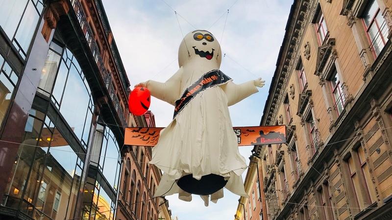 Mellan husen på drottninggatan i stockholm svävar ett över 2 meter stort uppblåsbart spöke i vitt som har en orange pumpa i handen. Det är utanför affären Buttericks.
