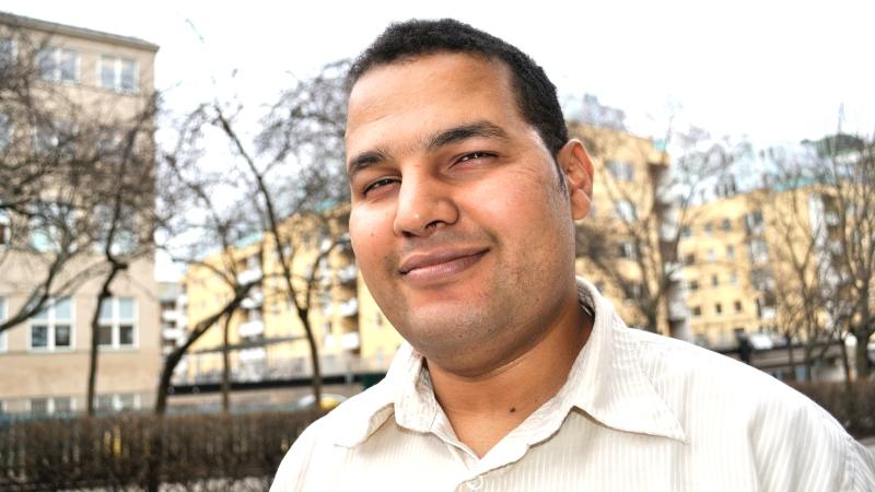 Hamaddah Mansour har kort, mörkt hår och en ljus skjorta.