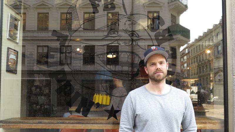 Jon Widegren står framför ett fönster till hans restaurang. På fönstret finns en stor dekal av en hamburgare med ansikte. Jon har keps och skäggstubb.