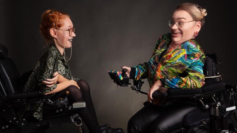 Två leende kvinnor i elrullstol sitter mittemot varandra