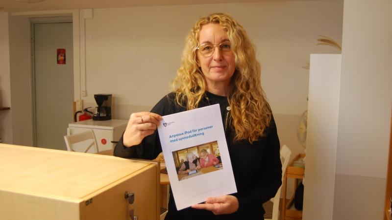 En blond långhårig kvinna håller i en broschyr, bakgrund kontor med hyllor