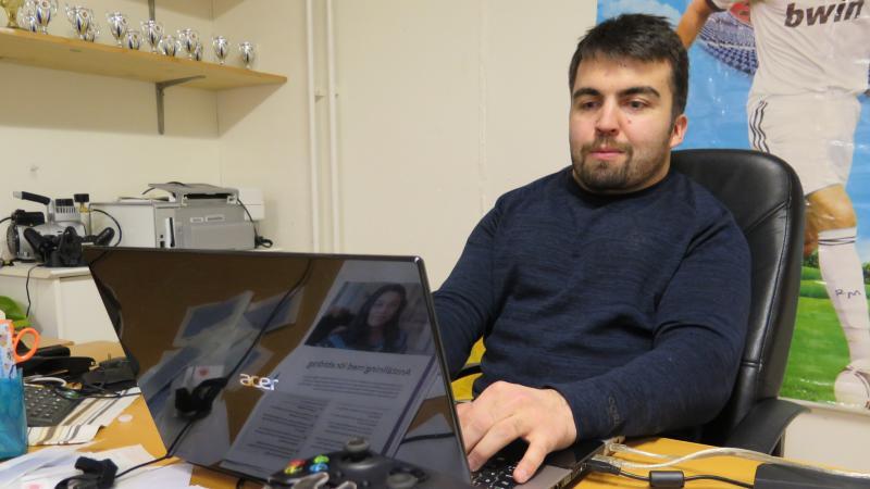Bild på Haydar Gürbüz framför datorn.