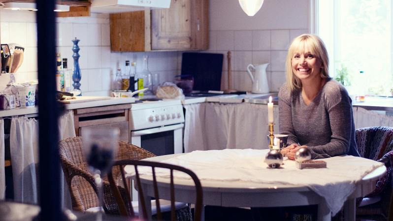 Tina Nordström sitter vid ett bord. Hon har ljust hår och lugg.