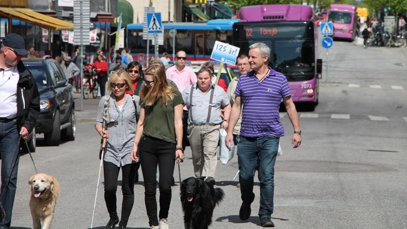 Några SRF:are går käpparaden tillsammans med ledarhund och ett plakat där det står 125 år. I bakgrunden syns en innerstadsbuss och annan trafik som snällt fick vänta medan paraden ägde rum.