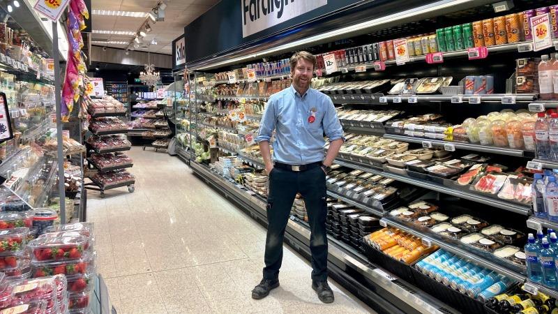Man i blå skjorta i butik, står mellan två höga matvaruhyllor