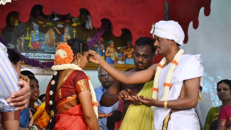 Hinduiskt bröllop. Brudgummen i turban och helt klädd i vitt lägger handen på brudens panna. Hon är helt klädd i rött och har blommar i håret.