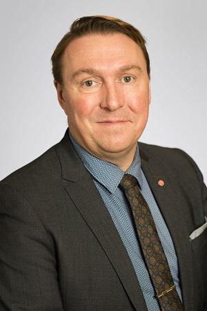 Porträttbild på man med kort mörkblont hår, klädd i grå kavaj och diskret mönstrad slips.