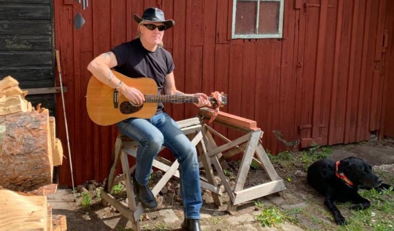 Johan Seige. Man i som glasögon med gitarr i knäet framför röd husvägg.