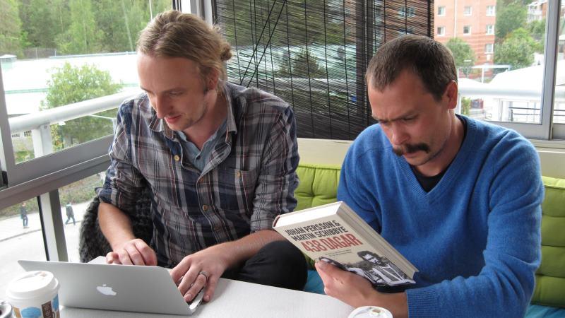 Två män sitter bredvid varandra vid ett litet vitt bord, vi ser dem framifrån. Den ena blond med håret uppsatt i en tofs. Han har gråblå rutig skjorta och skriver på sin laptop. Den andra har mycket kort brunt hår och mustasch, han har en blå långärmad stickad tröja. Han håller boken de skrivit tillsammans: 438 dagar.