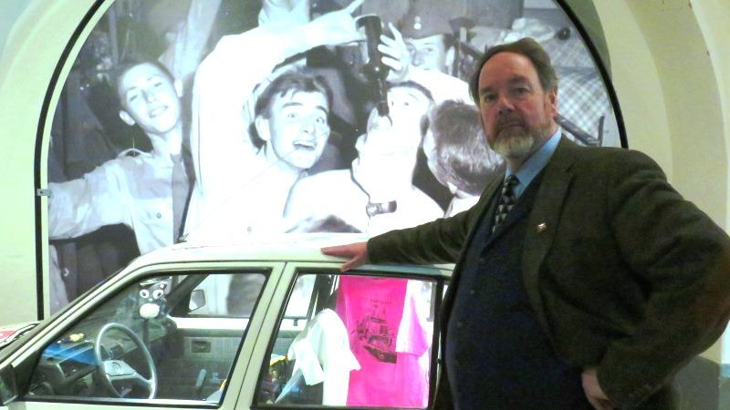 En man som står vid en bil.