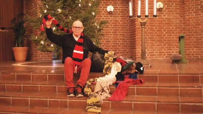 Skallig man med utsträckt arm sitter på stentrappa i  kyrka, bredvid en säck med halsdukar som väller ut.