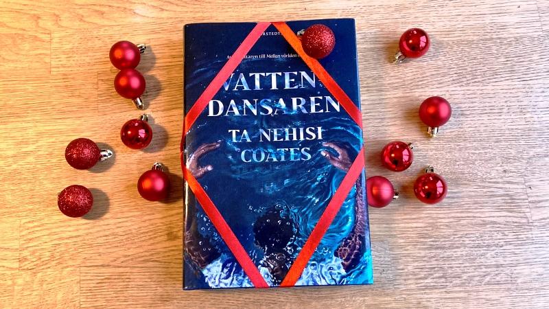 Blå bok  med rött band, på bord. Små röda julgranskulor bredvid