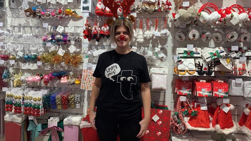 En brett leende Natalie Linde på Flying Tiger Copenhagen med renhorn och röd plastnäsa framför en vägg täckt av julprydnader.