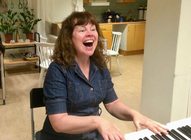 Körledaren Cecilia Åslund har långt brunt lockigt hår, sitter vid pianot och sjunger med öppen mun.