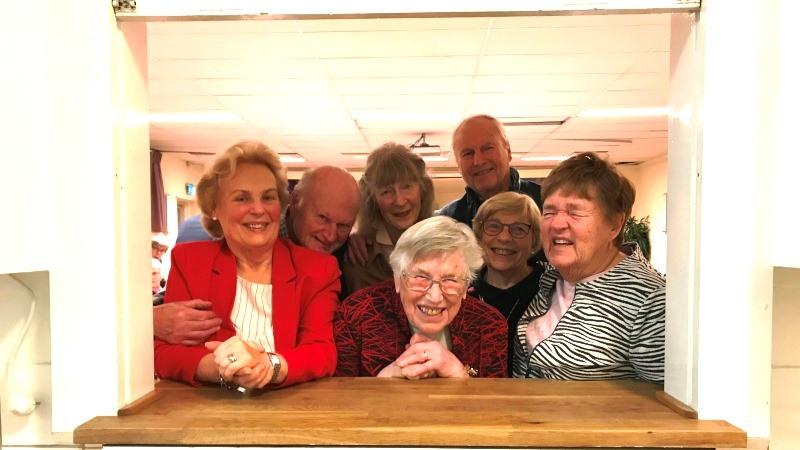 Några leende äldre män och kvinnor tittar in genom en serveringslucka.