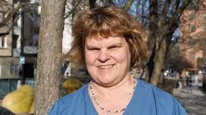 Rödbrunhårig leende kvinna, med blå blus, står ute vid park.