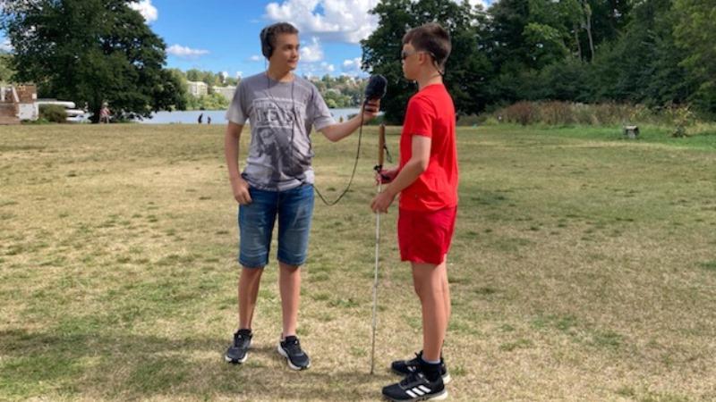 Två tonårskillar i shorts på grässlänt, sommar. Den ena håller i en mikrofon.