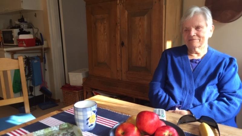 Äldre vithårig kvinna i blå kofta sitter vid matsalsbord.