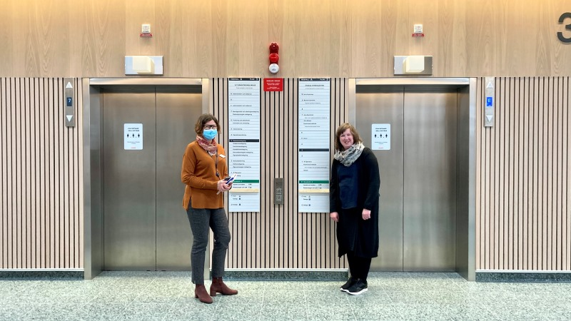 Två kvinnor framför två hissdörrar.