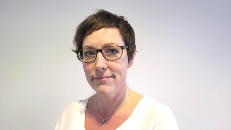 Kvinna med kort brunt hår, glasögon och vit blus.