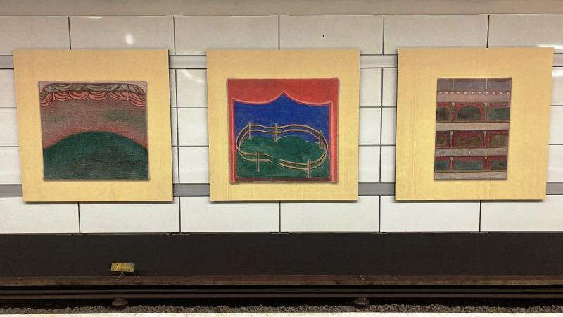 Tre tavlor med olika motiv och varmgula passpartouer av konstnären Lisa Lundgren hänger på en plattformsvägg över spåret.