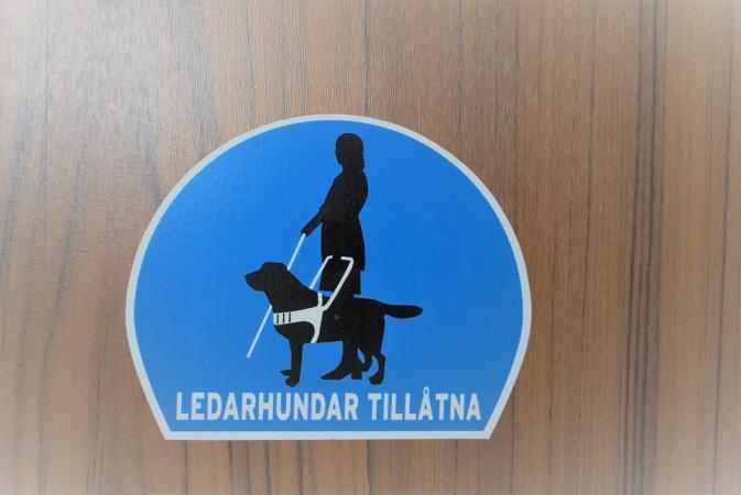 """Ett blått klistermärke med den vita texten """"Ledarhundar tillåtna"""" och en stiliserad bild på ett ledarhundsekipage. Klistermärket sitter på en dörr i träpanel."""
