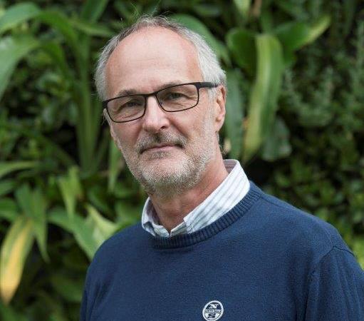 Man med fyrkantiga svarta glasögon, grått skägg och högt hårfäste klädd i blå tröja med skjorta under.