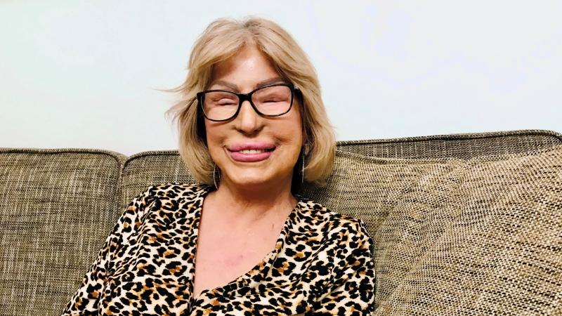 Leende kvinna med ljus page och glasögon, sitter i en soffa