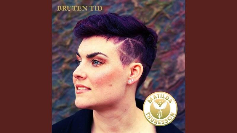 Korthårig kvinna i profil med brunt hår. Bergvägg bakom.