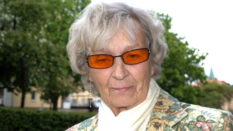 Maud Tillgren har grått, ganska kort hår, orangea glasögon, mönstrad kavaj och vit scarf.