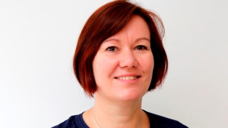 Porträttbild på en leende kvinna med kortklippt frisyr i olika mörkröda nyanser.