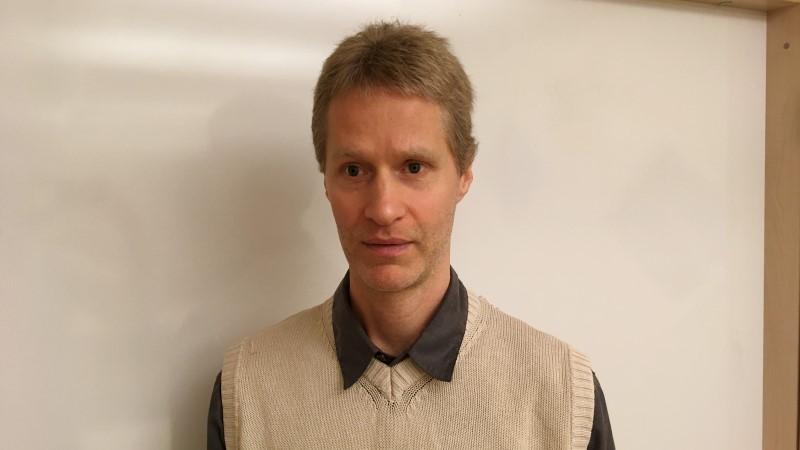 Mellanblond man, kort hår med beige slipover framför en whitboardtavla