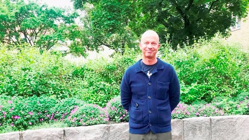 Leende man utan hår klädd i blå tröjorna står med armarna bakom ryggen framför en låg mur och grönska i bakgrunden.