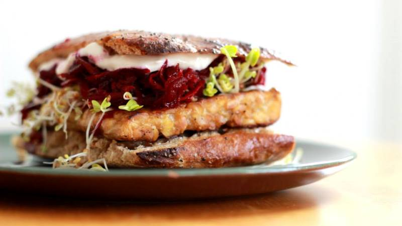 Bild på hamburgare med tunnt mörkt surdegsbröd, grönsaker och vad som liknar en stor ostbit i mitten.