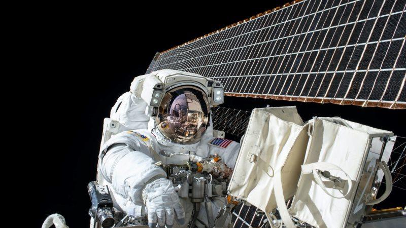 Vitklädd astronaut jobbar med solpanel i rymden
