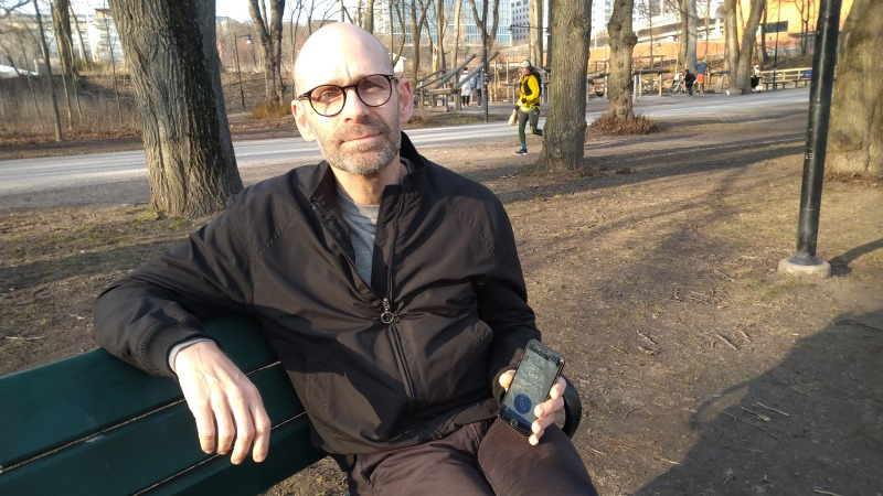 En skäggig man med glasögon och kalt huvud sitter på en parkbänk med en mobiltelefon i handen där man skymtar SOS Alarm-appen.