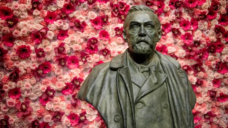 Byst av Alfred Nobel, står framför vägg dekorerad med röda, rosa rosor