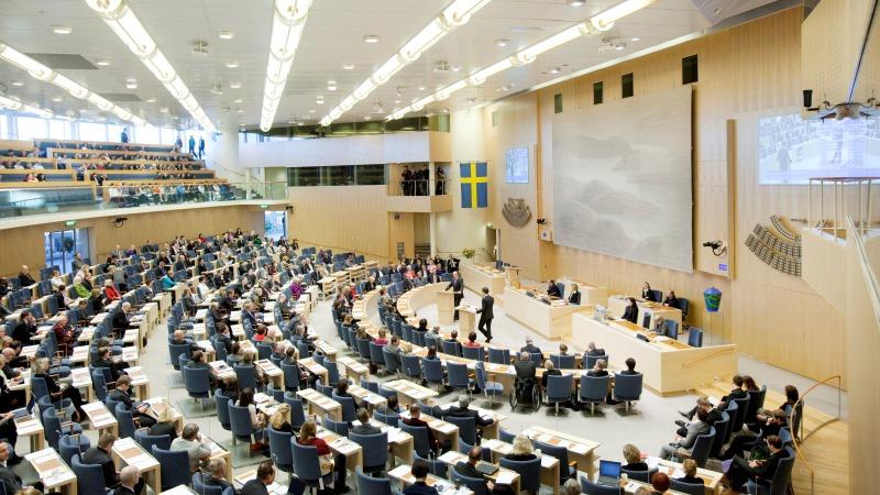 Riksdagsledarmöter som sitter och lyssnar på två debattörer inne i Sveriges riksdag.