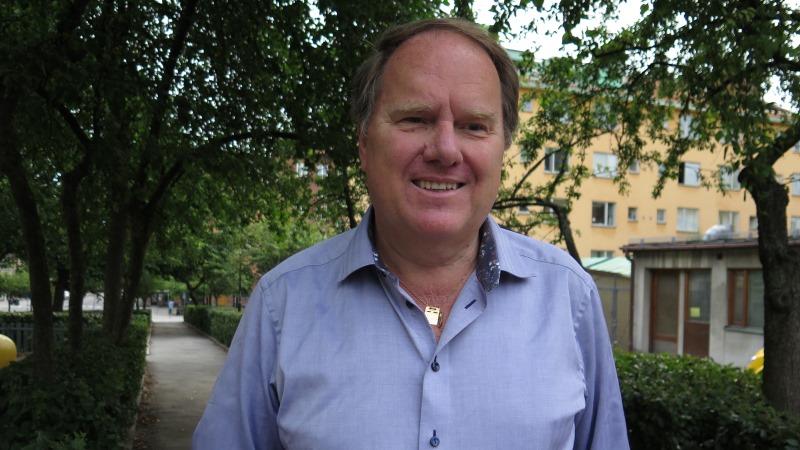 Per Karlström har blå uppknäppt skjorta och är omgiven av grönska.