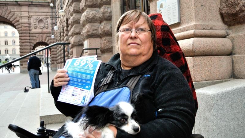 Madde Palmgren har kort blont hår och ovala glasögon. Hon sitter med en liten hund i famnen utanför Riksdagshuset med blå flygblad i handen där man ser texten 89 procent.