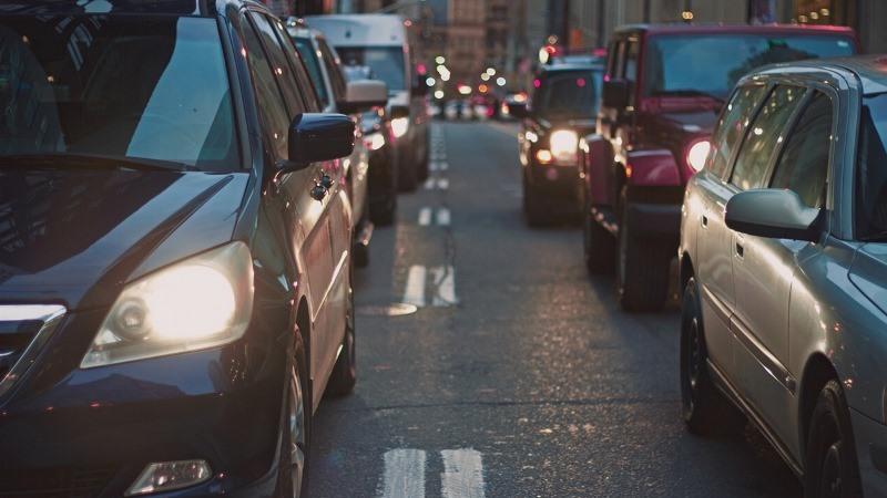 Två körfält med bilar på rad. Suddig stadsmiljö bakom.