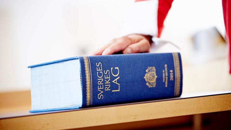 En hand ligger på den tjocka blå lagboken med texten SVERIGES RIKES LAG i guldtext på ryggen.