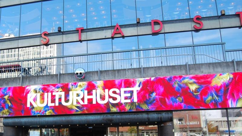Skylt på glasfasad med vita versaler KULTURHUSET mot bakgrund av starka röda, blå och gula färger i abstrakt mönster.