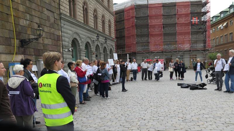 Människor som står på ett torg. De håller i plakat.
