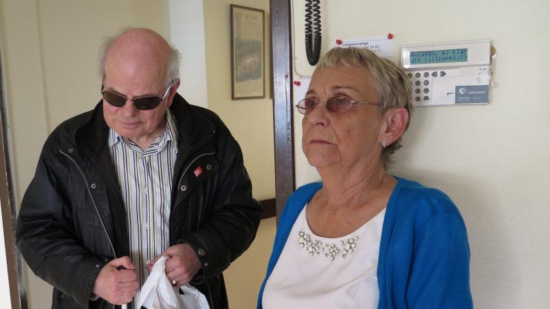 Barbro har kort ljust hår och en stickad blå tröja, Peter har en svart skinnjacka, glasögon och tunnt grått hår.