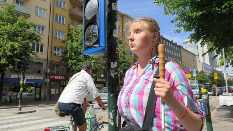 En kvinna under trafikljuset, som är blått med två cirklar där lampor visar siffror.