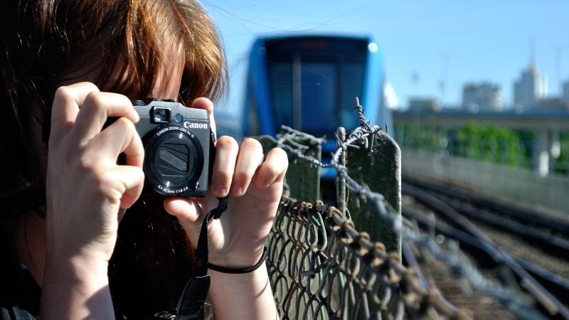 En kvinna filmar ett blått tunnelbanetåg.