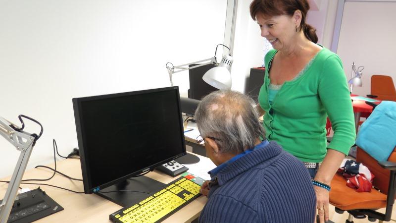 Två personer som hjälps åt vid en anpassad dator med ett gult tangentbord.