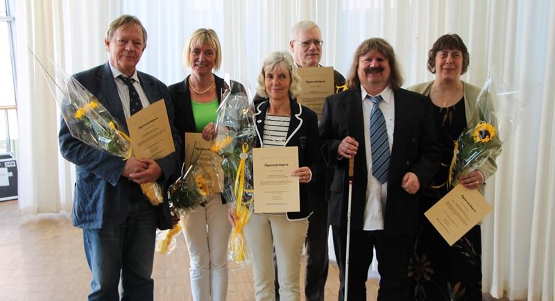 Fem pristagare fotas tillsammans med Håkan Thomsson, ordförande i SRF. De håller blommor och ler.