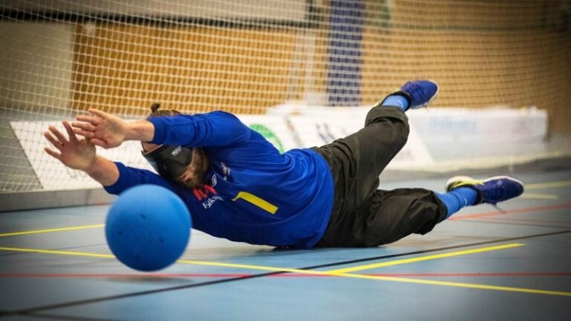 En goalballspelare slänger sig raklång för att fånga en boll på väg.